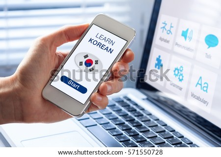 Learn Korean language online concept with a person showing e-learning app on mobile phone with the flag of South Korea #571550728