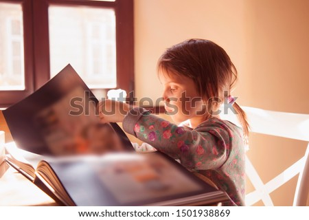 Learn аlways and everywhere. Cute little child girl watching a book. Science, education, knowledge, self-improvement, success concept.
