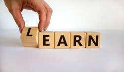 Learn or earn. Hand flips a cube and changes the word 'earn' to 'learn' or vice versa. Beautiful white background. Business concept. Copy space.