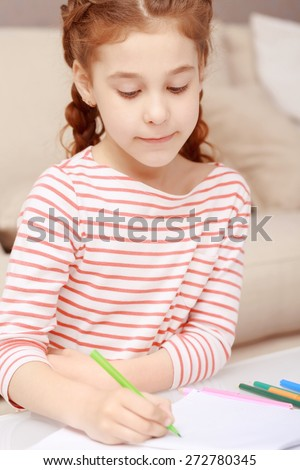 Learn to draw. Portrait of little concentrated girl sitting still and drawing with colorful crayons.