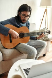 Learning a new instrument. Young focused man wearing glasses sitting on sofa at home and learning how to play guitar, watching online course on laptop. Distance education. Focus on a man. Stay home