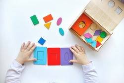 Learning colors and shapes. Children's wooden toy. The child collects a sorter. Educational logic toys for kid's. Children's hands close-up. Montessori Games for Child Development.