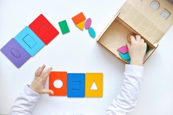 Learning colors and shapes. Children's wooden toy. The child collects a sorter. Educational logic toys for kid's. Kindergarten educational toys, Cognitive skills, Learn Through Play tools concept.