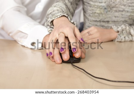 Learning computer skills.\ Female hand over the male hand directing his moves with computer mouse.\ Desk, table, beige, worm, nail make-up on woman fingers. Blurred people body on background.