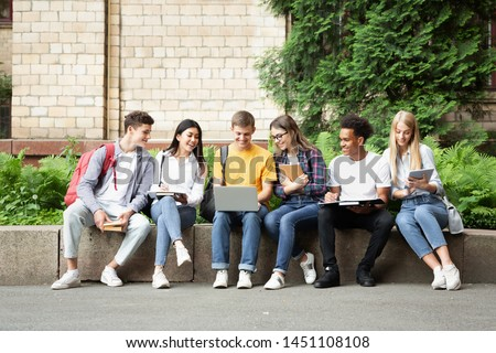 Learning concept. Students doing group project on laptop, sitting in university campus
