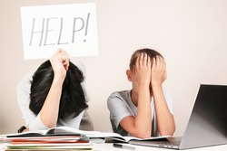 Learning difficulties, remote education, online learning and working at home. Tired mother and sad kid need help to do homework