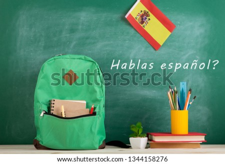 Learning languages concept - green backpack, blackboard with text 'hablas espa?ol', flag of the Spain, books and school supplies Foto stock ©