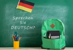 Learning languages concept - green backpack, blackboard with text