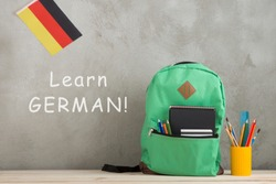 Learning languages concept - green backpack, flag of the Germany, school supplies against a cement wall with text