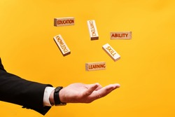 learning skills concept. a man throws up wooden blocks with the inscriptions skill, knowledge, ability, competence, education
