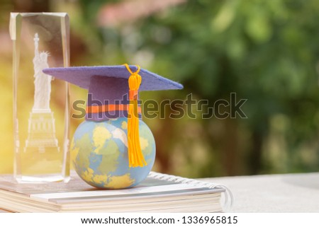 Learning study international abroad in America concept: Graduate cap on earth world globe model map on book with blur of USA Statue of Liberty crystal souvenir. Idea of Work and Travel studies program