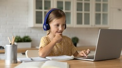 Learning time. Interested little kid schoolgirl in headset sit at home desk watch education video lesson. Curious small school age girl think on teacher question select correct answer on laptop screen