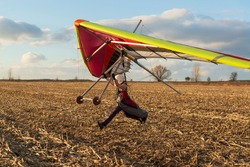 Learning to fly. Beginner student pilot runs fast with hang glider wing.