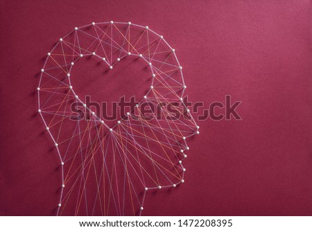 Learning to love concept. Network of pins and threads in the shape of a cut out heart inside a human head symbolising that love is the core of our being and has its own logic. Foto stock ©