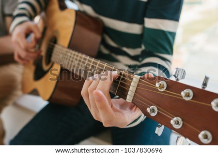 Learning to play the guitar. Music education and extracurricular lessons. Hobbies and enthusiasm for playing guitar and singing songs. #1037830696