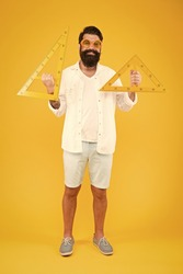 Learning triangles is easy here. Happy bearded man holding triangles on yellow background. School teacher or student smiling with geometric triangles for geometry lesson. Lesson in triangles.