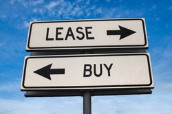 Lease vs buy. White two street signs with arrow on metal pole with word. Directional road. Crossroads Road Sign, Two Arrow. Blue sky background. Concept for own property versus borrow it.