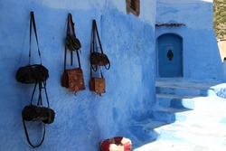 Leather bags hanging on a blue wall in Chefchaouen, Morocco