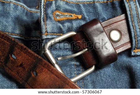 Leather belt unbuckled on a pair of blue jeans