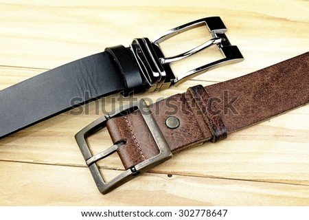 Leather belt with a buckle on a wooden board. Men fashion. Men accessories.