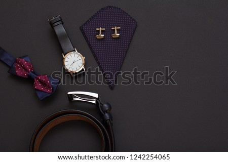 Leather belt with metal buckle, bow tie, watch with a black leather strap and handkerchief with cufflinks on black background. Accessories for men. Top view.