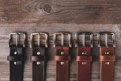 Leather belts in different colors for jeans and chinos on the wooden surface.