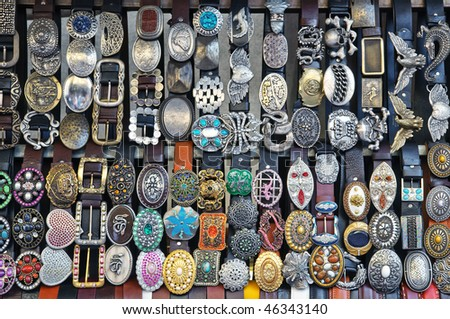 Leather belts with colorful buckles for sale on street market in Florence, Italy - stock photo