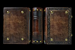 Leather book with embossed frame and metal pins in the corners Captured isolated over the black background