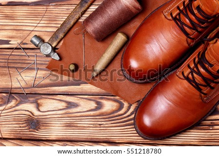 Leather boots and bootmaker tools awl, nails, skien of thread .Wooden background.Concept tools bootmaker.top view. copy space