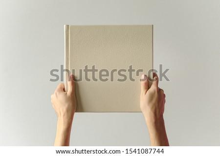 leather bound photo album in hand. Mock up photobook. design concept. Сток-фото ©