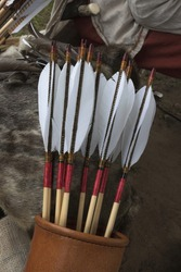 Leather bow quiver filled with arrows with graven woodnock and traditional natural fletching as archery concept.