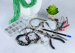 Leather bracelet consisting of beads of various colors, metals, tools and many tools used to make jewelry on the table.