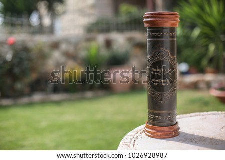Leather case with the inscription 'Scroll of Esther', encasing the Jewish book of Esther, with a garden backround. Jews read the book of Esther, as part of the traditions of the holiday of Purim Foto stock ©