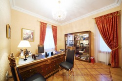 Leather chairs and gilt table with lamp in home office in classic style.