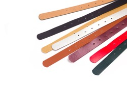 Leather colored belts on a white background top view. There is free space for your inscription.