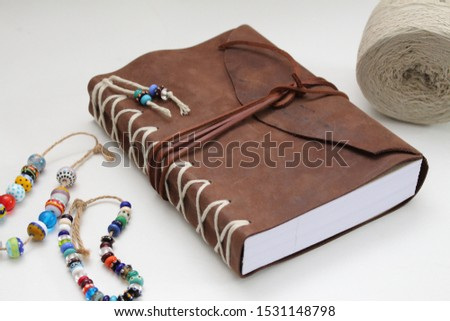 leather cover of handmade book with handmade bead on white background #1531148798