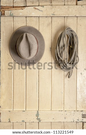 leather cowboy hat and rope hanging on an old weathered door