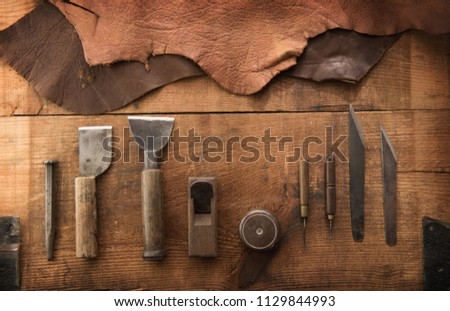 Leather craft or leather working. Leather working tools and cut out pieces of brown leather on craftman's work desk .