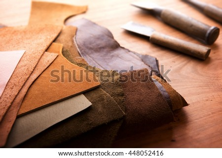 Leather craft or leather working. Selected pieces of beautifully colored or tanned leather on leather craftman\'s work desk . Piece of hide and working tools on a work table.