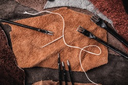 Leather Crafting, Artisan Crafts, Handmade Leather Tools with Wax Cord and Needle. Leather Pieces Workspace, Background Wallpaper and Textured.