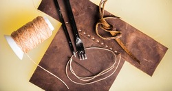 Leather Crafting, Handcrafts Work, Handmade Leather Tools with Dark Brown Leather with Wax Cord and Metal tools on hard board workspace.