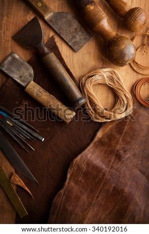 Leather craftmans work desk . Piece of hide, thread and working tools on a work table. Intentionally shot in low key.