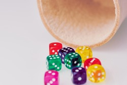 leather dice cup with a lot of colored dice on white background