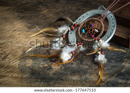 Leather dream catcher and horseshoe on wooden floor