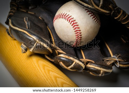 Leather glove with baseball and bat over white background