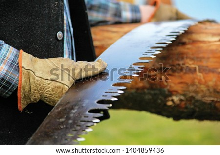 Leather Gloved Hand Holding Old Fashoned Antique Cross Cut Lumber Saw Blade Close up