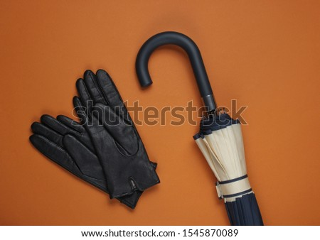 Leather gloves and an umbrella on brown background. Top view