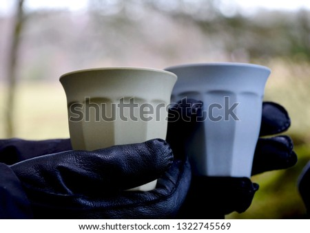 Leather gloves holding coffee cups outside in the forest. Photo taken in Sweden