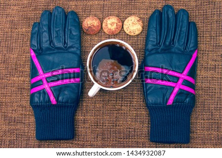leather gloves next to a hot cup of coffee. hot drinks