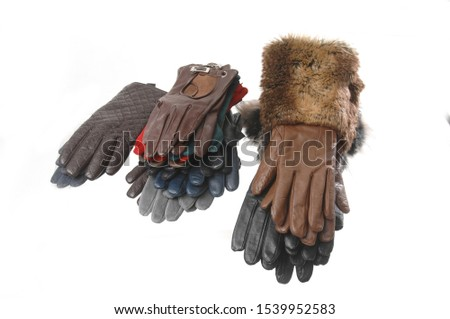 Leather gloves on a white background. A stack of multi-colored leather gloves on a white background.